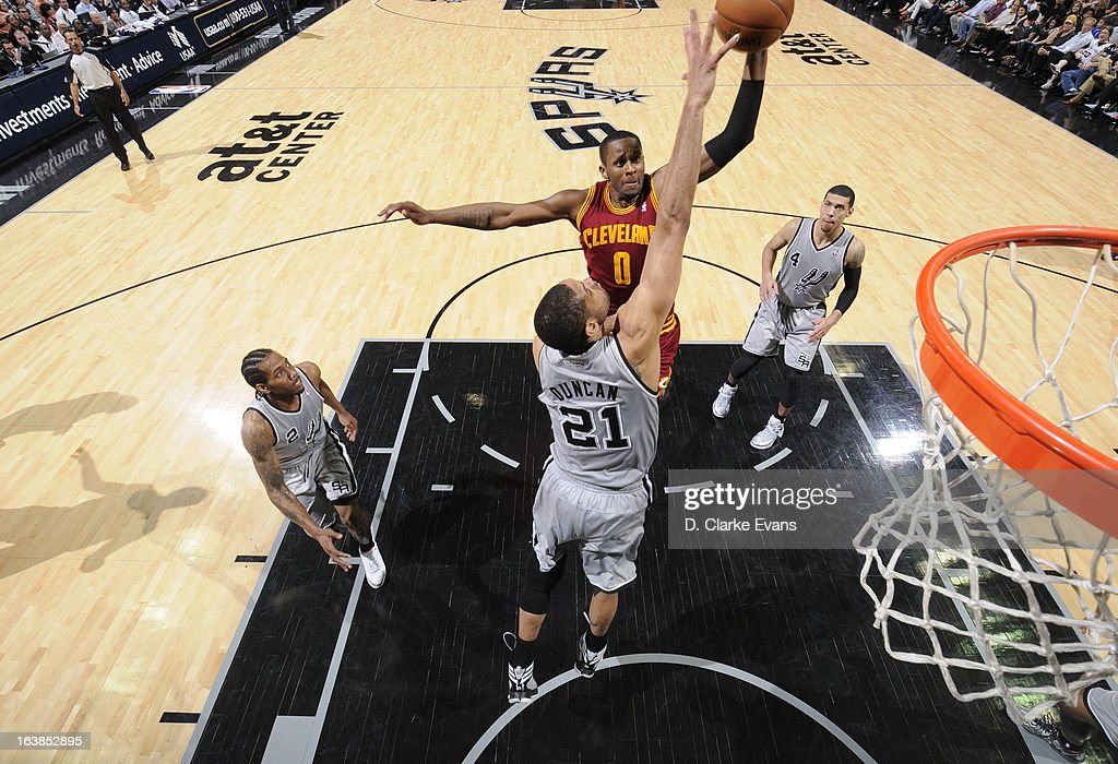 C.J. Miles #0 of the Cleveland Cavaliers goes to the basket against Tim Duncan #21 of the San Antonio Spurs during the game between the Cleveland Cavaliers and the San Antonio Spurs on March 16, 2013 at the AT&T Center in San Antonio, Texas.