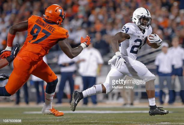 Miles Sanders of the Penn State Nittany Lions runs the ball as Bobby Roundtree of the Illinois Fighting Illini pursues during the game at Memorial...