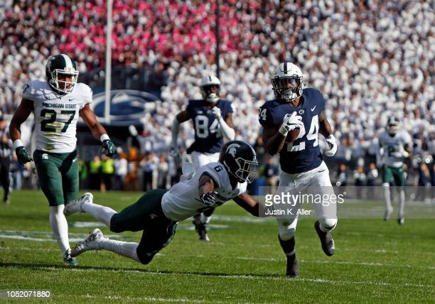 Miles Sanders of the Penn State Nittany Lions rushes for 78 yards against Khari Willis of the Michigan State Spartans and David Dowell of the...