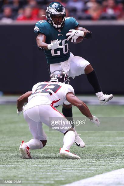 Miles Sanders of the Philadelphia Eagles leaps over Fabian Moreau of the Atlanta Falcons during the fourth quarter at Mercedes-Benz Stadium on...