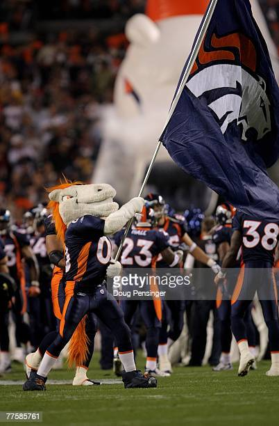 Miles the mascot escorts the Denver Broncos onto the field prior to facing the Green Bay Packers at Invesco Field at Mile High on October 29 2007 in...