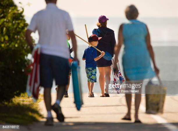 Miles Thebarge of Brunswick carries his shovel and rake while walking down Ocean AVenue to Higgins Beach in Scarborough with his brother Declan and...