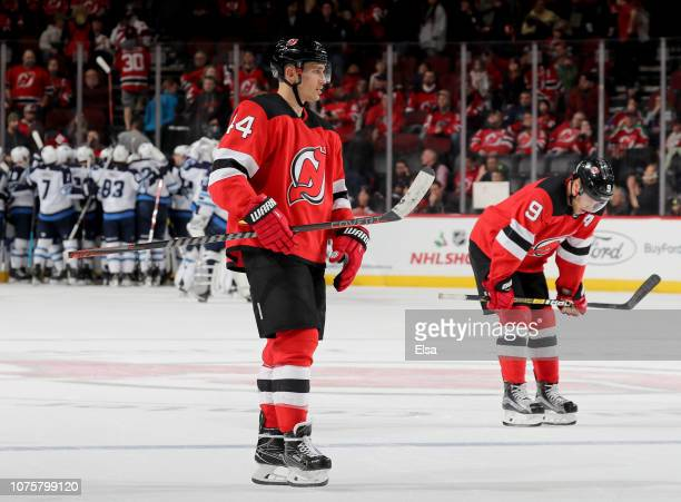 Miles Wood and Taylor Hall of the New Jersey Devils skate off the ice after the loss to the Winnipeg Jets at Prudential Center on December 01 2018 in...