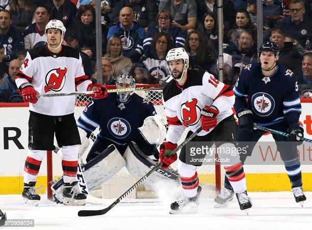 Miles Wood Drew Stafford of the New Jersey Devils goaltender Connor Hellebuyck and Dmitry Kulikov of the Winnipeg Jets keep an eye on the play at the...