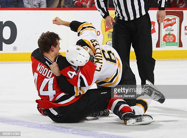 Miles Wood of the New Jersey Devils and Colin Miller of the Boston Bruins fight during the first period at the Prudential Center on January 2 2017 in...