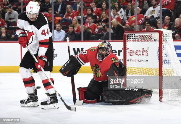 Miles Wood of the New Jersey Devils and goalie Corey Crawford of the Chicago Blackhawks watch the puck in the second period at the United Center on...