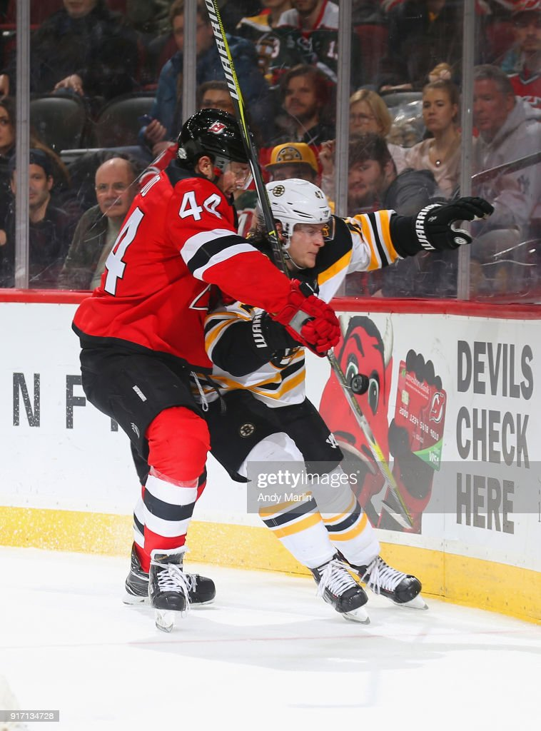 Miles Wood #44 of the New Jersey Devils and Torey Krug #47 of the Boston Bruins battle for position during the game at Prudential Center on February 11, 2018 in Newark, New Jersey.