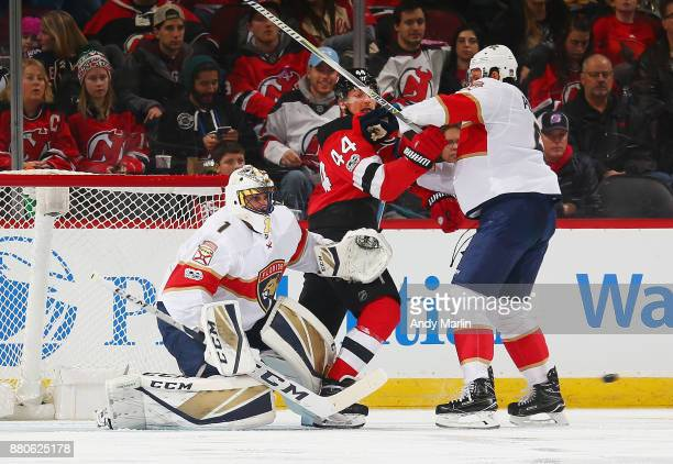 Miles Wood of the New Jersey Devils battles against Alex Petrovic of the Florida Panthers in front of Roberto Luongo during the game at Prudential...