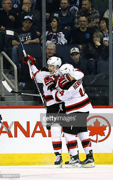 Miles Wood of the New Jersey Devils is all smiles as he celebrates his first career NHL goal with teammate Adam Henrique during third period action...