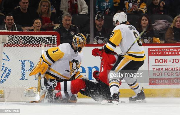 Miles Wood of the New Jersey Devils is checked by Brian Dumoulin as Casey DeSmith of the Pittsburgh Penguins looks on during the game at Prudential...