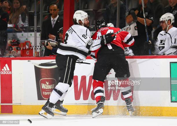 Miles Wood of the New Jersey Devils is checked into the boards by Drew Doughty of the Los Angeles Kings during the game at Prudential Center on...
