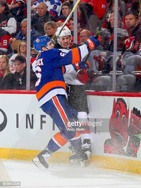 Miles Wood of the New Jersey Devils is checked into the boards by Ryan Pulock of the New York Islanders during the game at Prudential Center on...