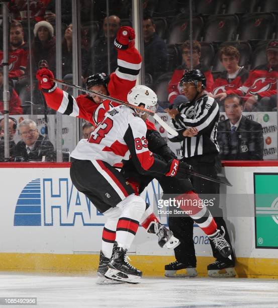 Miles Wood of the New Jersey Devils is hit by Christian Jaros of the Ottawa Senators during the second period at the Prudential Center on December 21...