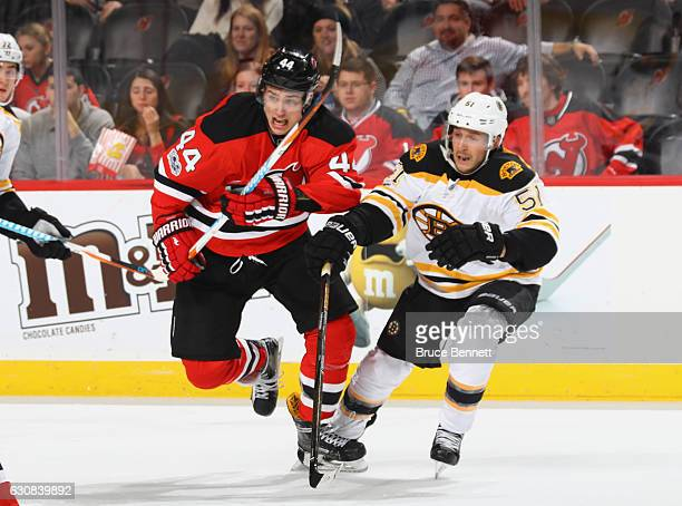 Miles Wood of the New Jersey Devils is pursued by Ryan Spooner of the Boston Bruins at the Prudential Center on January 2 2017 in Newark New Jersey...