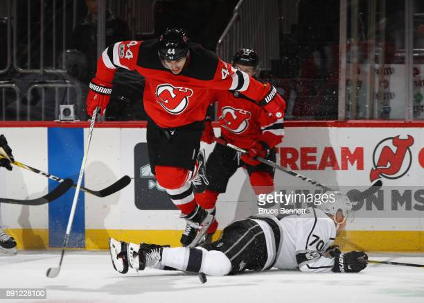 Miles Wood of the New Jersey Devils jumps over Tanner Pearson of the Los Angeles Kings during the first period at the Prudential Center on December...