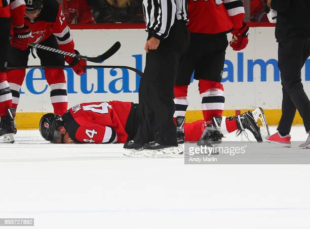 Miles Wood of the New Jersey Devils lays on the ice arfter being injured against the Dallas Stars during the game at Prudential Center on December 15...