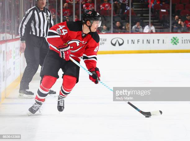 Miles Wood of the New Jersey Devils plays the puck against the Winnipeg Jets during the game at Prudential Center on March 28 2017 in Newark New...
