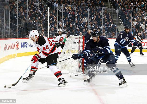 Miles Wood of the New Jersey Devils plays the puck behind the net as Paul Postma of the Winnipeg Jets gives chase during first period action at the...