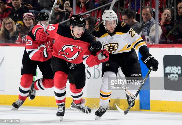 Miles Wood of the New Jersey Devils skates against Brandon Carlo of the Boston Bruins during the third period at Prudential Center on February 11...