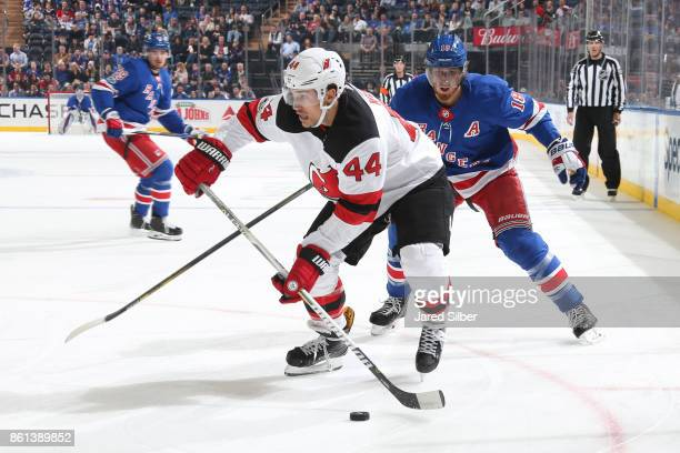 Miles Wood of the New Jersey Devils skates with the puck against Marc Staal of the New York Rangers at Madison Square Garden on October 14 2017 in...