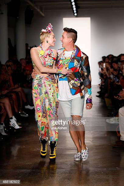 Miley Cyrus and designer Jeremy Scott walk the runway at the Jeremy Scott fashion show during MADE Fashion Week Spring 2015 at Milk Studios on...