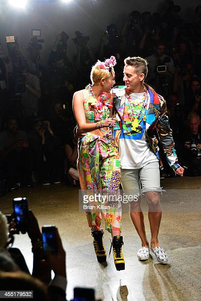 Miley Cyrus and designer Jeremy Scott walk the runway together at the conclusion of Jeremy Scott during MADE Fashion Week Spring 2015 at Milk Studios...