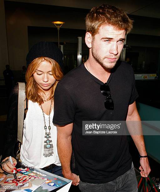 Miley Cyrus and Liam Hemsworth arrive at LAX airport on June 21 2010 in Los Angeles California