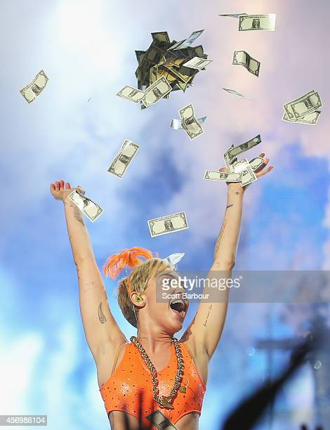 Miley Cyrus throws money in the air as she performs at the opening night of her Bangerz Tour in Australia at Rod Laver Arena on October 10 2014 in...