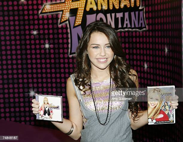 Miley Cyrus who plays the Disney character Hannah Montana poses with the Hannah Montana 2 CD and Hannah Montana Pop Star Profile DVD at the World of...