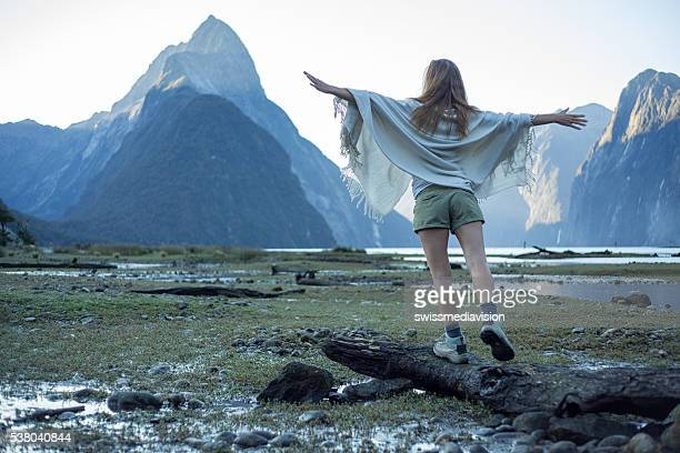 Milford Sound : Woman stands on tree trunk