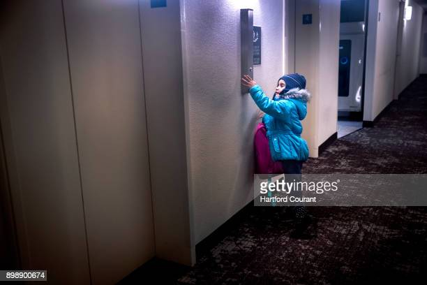 Milianis Rivera runs out of her room at the Red Roof Inn in Hartford Conn to push the button for the elevator on December 21 2017 Before going to...