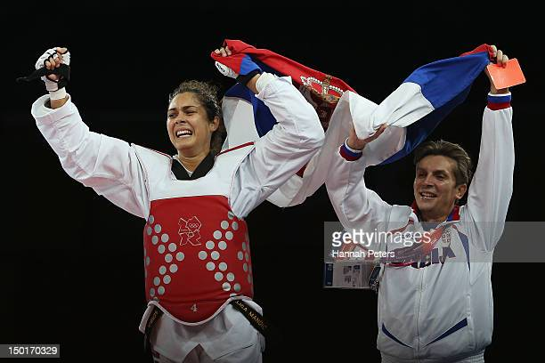 Milica Mandic of Serbia celebrates with her coach after beating AnneCaroline Graffe of France during the Women's 67kg Taekwondo Gold medal match on...