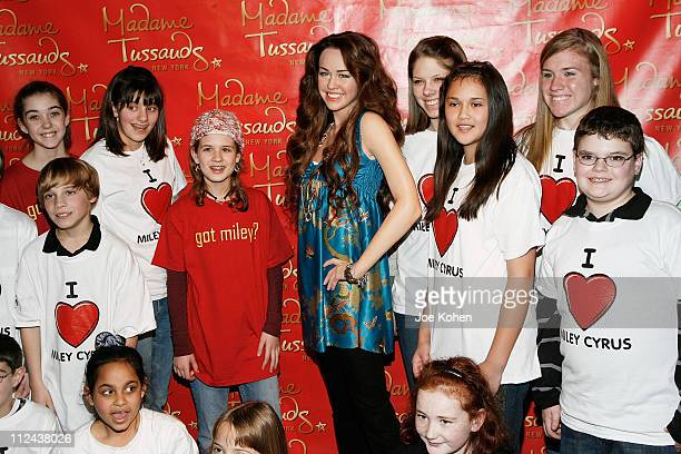Miliey Cyrus fans pose for a photo with the figure of singer Miley Cyrus at Madame Tussauds and on March 20 2008 in New York City