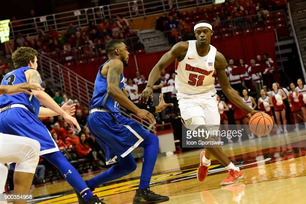 Milik Yarbrough forward Illinois State University Redbirds drives across the threepoint line against Qiydar Davis guard Indiana State Sycamores...