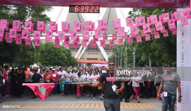 Milind Soman model and actor and women athletes participate during the Pinkathon run India's biggest women run at Jawahar Lal Nehru Stadium on...