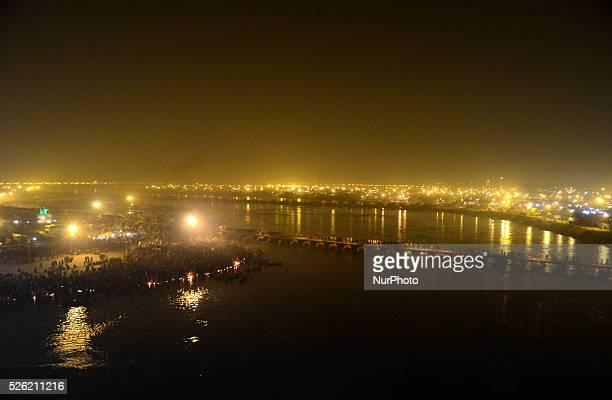 Milions of Indian Hindu devotees walk across a pontoon bridge at the Sangam the confluence of the Ganges Yamuna and the mythical Saraswati as others...