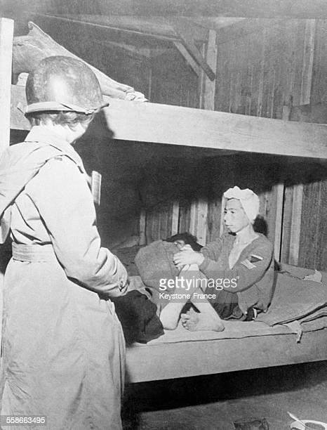 Militaire à côté d'une jeune femme déportée du camp de Penig en Allemagne sur un lit superposé du baraquement un triangle sur le bras en mai 1945