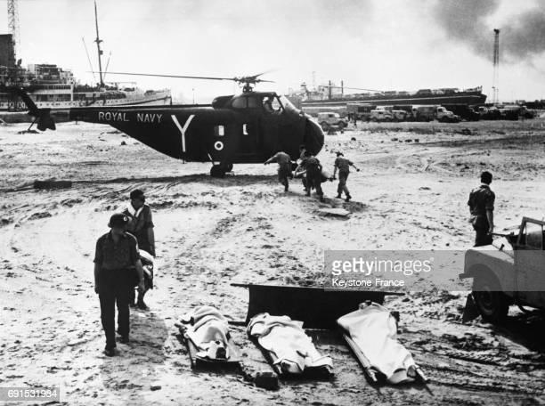 Militaires transportant un blessé sur un brancard vers un hélicopère de la Royal Navy pendant la crise de Suez à PortSaïd Egypte le 10 novembre 1956
