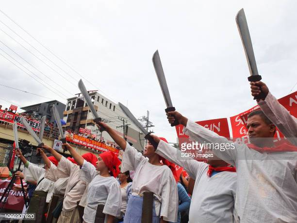 MENDIOLA MANILA PHILIPPINES Militant activists dressed as Andres Bonifacio are seen raising their bolos during the protest Leftist groups stage...