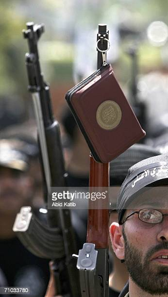 A militant from the AlAqsa Martyr's Brigade a group linked to Palestinian President Mahmoud Abbas' Fatah Movement holds a rifle with the holy Koran...