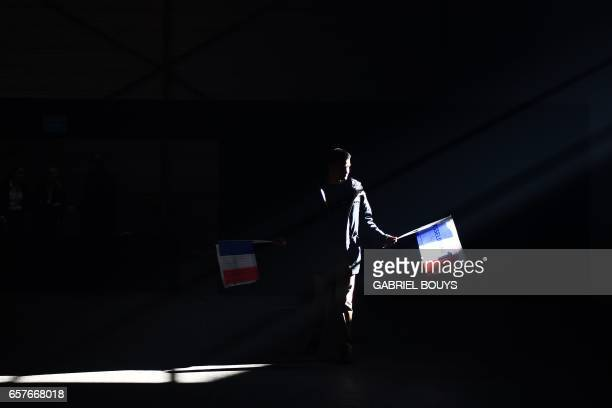 TOPSHOT A militant holds campaign flags as he arrives to attend a meeting of French presidential election candidate for the Popular Republican Union...