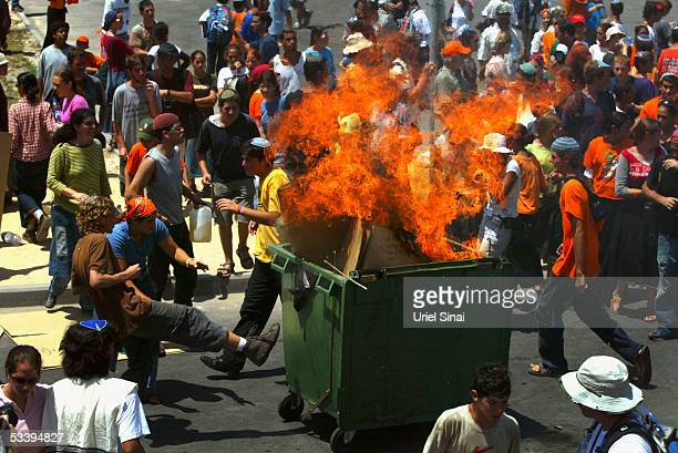 Militant Jewish settler extremists torch a garbage container during clashes with Israeli police who tried to secure the entry of shipping containers...