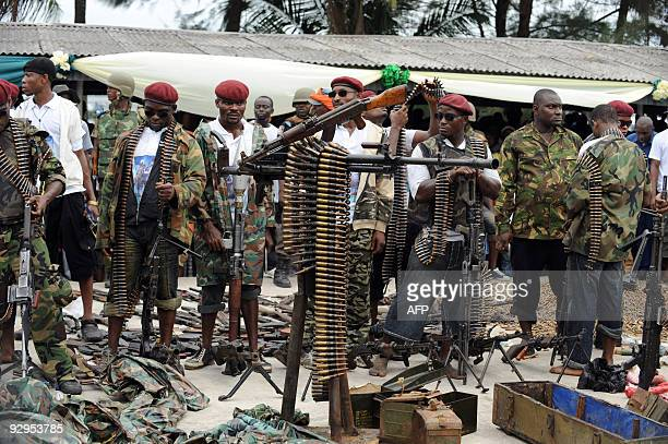 Militant youths display arms and ammunition surrendered by the most notorious leader of the militant groups in the Niger Delta Ateke Tom in Port...