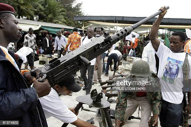 Militant youths tries to display arms and ammunition surrendered by the most notorious leader of the militant groups in the Niger Delta Ateke Tom in...