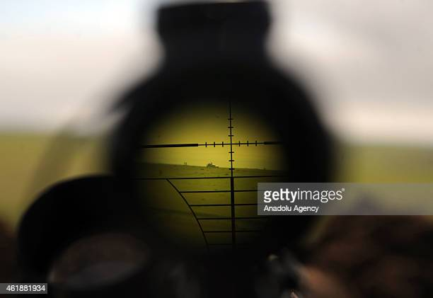 ISIL militants are seen through binoculars of a rifle during clashes between Islamic State of Iraq and the Levant militants and Peshmerga in Mawara...