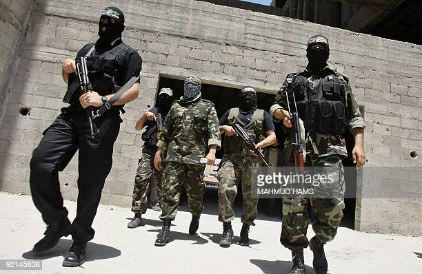 Militants escort Abu Obeida a spokesman for Hamas's armed wing the Ezzedine AlQassam Brigades as he arrives to hold a press conference in Gaza City...