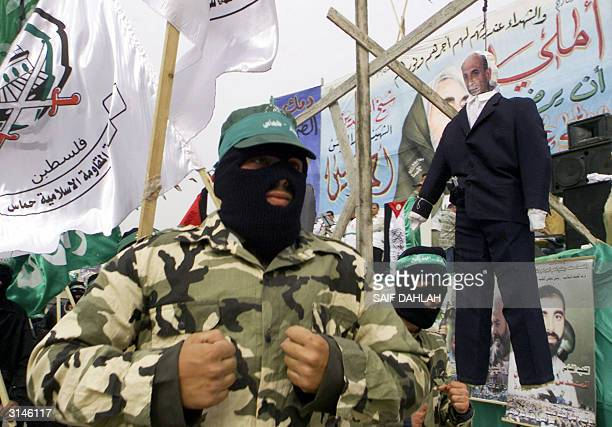 Militants from the radical Islamic group Hamas jog during a rally past an effigy of Israeli Defence Minister Shaul Mofaz hanging at a makeshift...
