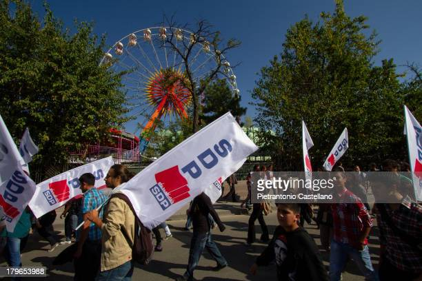 Militants holding flags of the Socialist Democracy Party pass in front of Ankara's Luna Park on their way to join Alevis' protest against...