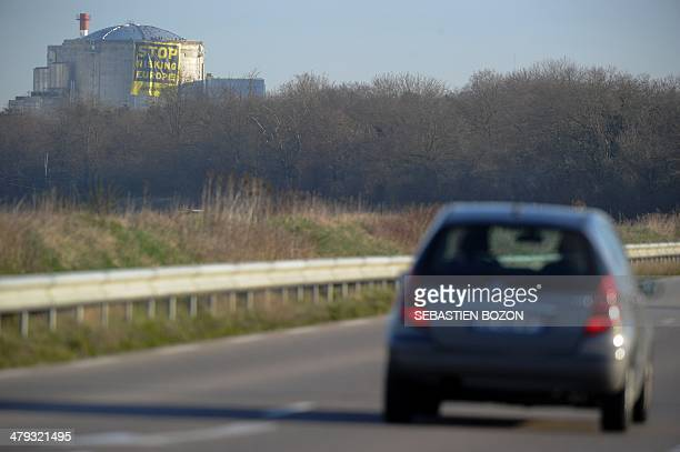 Militants of Greenpeace deploy a banner reading 'Stop risking Europe' on a reactor of the nuclear power plant of Fessenheim on March 18 2014 Several...