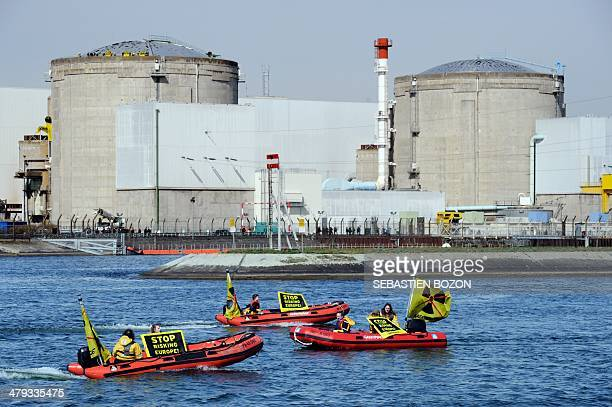 Militants of Greenpeace hold banners reading 'Stop risking Europe' in boats in front of the nuclear powerplant of Fessenheim on March 18 2014 Several...